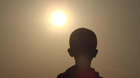 Silhouette boy, children and sun. Dream, hope and boyhood concept. The boy is watching sunset and Live Action