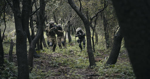 Squad of fully armed commando soldiers during combat in a forest scenery Live Action