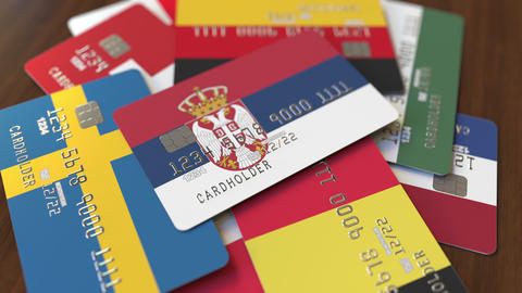 Many credit cards with different flags, emphasized bank card with flag of Serbia Live Action