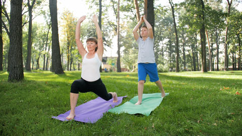 4k slow motion video of middle aged woman teaching teenage boy in yoga class Footage