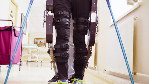 Legs of invalid in robotic exoskeleton walking through the corridor Live Action