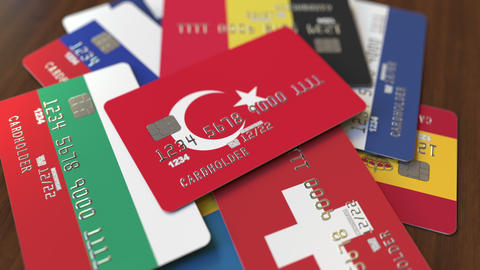 Many credit cards with different flags, emphasized bank card with flag of Turkey Live Action