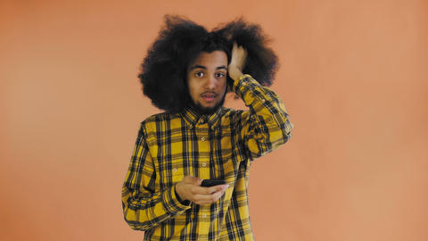 Young sad Afro-American man using phone and getting bad news on Orange Live Action