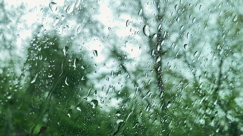 Rain drops on window glasses surface with cloudy background. Driving in rain Footage