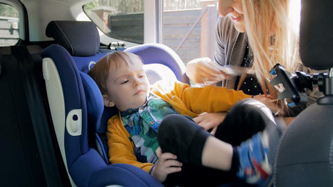 4k video of young mother seating her little son in child safety seat and adjusts Live Action