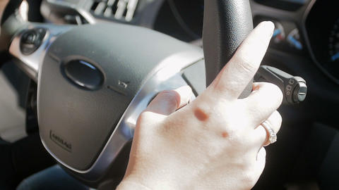 Closeup slow motion video of female driver presseing knobs on steering wheel and Footage