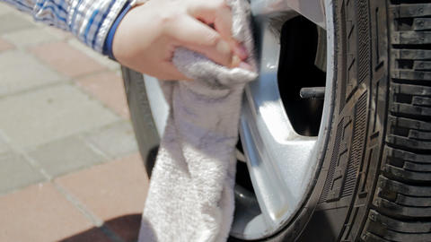 4k footage of man cleaning and polishing dirty wheels on his car at house Footage
