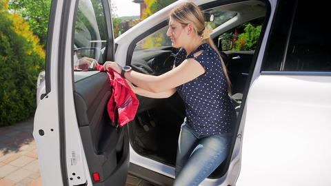 Slow motion video of young woman cleaning her car with cloth. Driver polishing Footage
