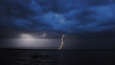 Thunderstorm and lightning over lake in the night Archivo