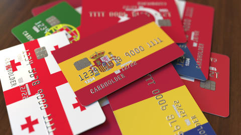 Many credit cards with different flags, emphasized bank card with flag of Spain Footage