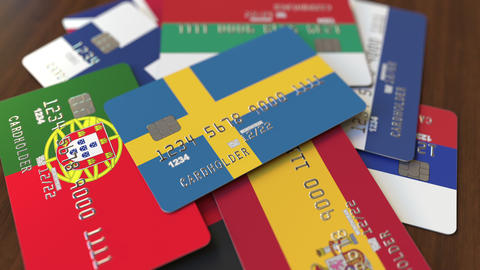 Many credit cards with different flags, emphasized bank card with flag of Sweden Footage