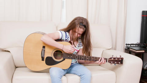 Teenage girl plays on an acoustic guitar sitting on a sofa Live Action