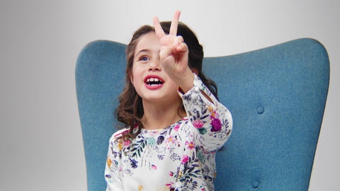 little girl in dress talks and counts with fingers on chair Archivo
