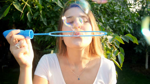 Closeup slow motion footage of colorful soap bubbles flying in the camera. Young Footage