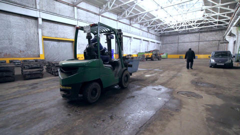 man drives forklift vehicle with container along warehouse Footage
