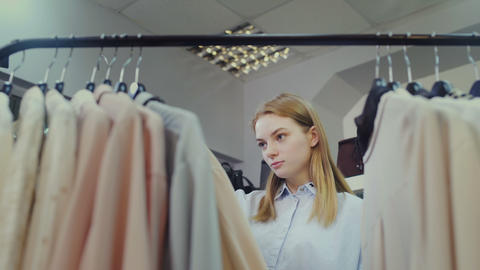 Young woman looking at clothing, hanging on hangers Footage