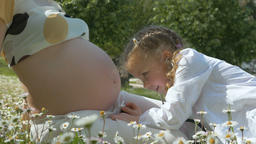 Cute kid girl examining pregnant mother belly Footage