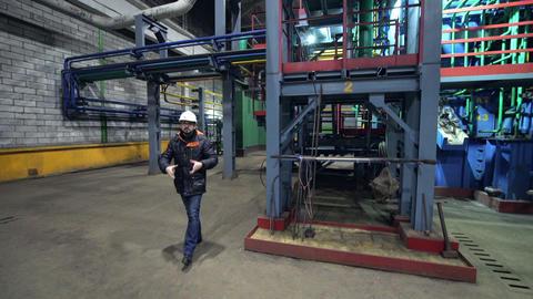 engineer in helmet talks and walks along plant workshop Archivo