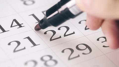 Marking the twenty-second 22 day of a month in the calendar with a red marker Live Action