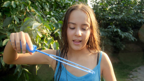 Slow motion video of smiling teenage girl in park blowing soap bubbles in camera Footage