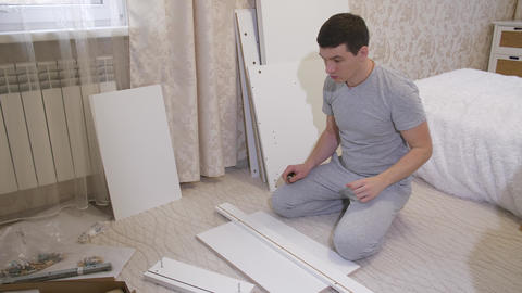 Man with parts of furniture Footage