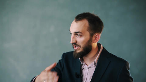 Bearded man in jacket and striped shirt gesturing while talk on isolated wall Live Action
