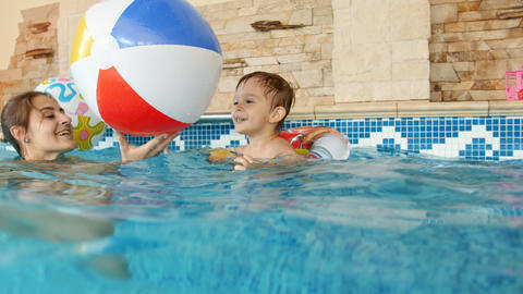 4k video of happy mother with child playing in indoor swimming pool with Footage
