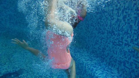 4k video of two teenage girls diving underwater at indoor swimming pool Footage