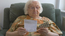 An old woman reads a medicine leaflet Footage