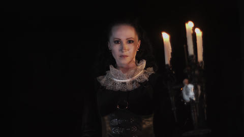Baroness in victorian style dress standing in dark room with candelabrum Footage