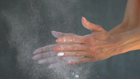 Muscular woman clapping hands with talc powder in a gym Live Action