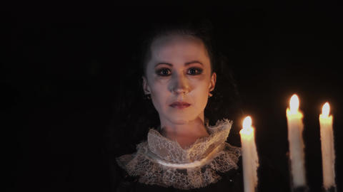Portrait of woman in victorian dress standing in dark room with candelabrum Footage