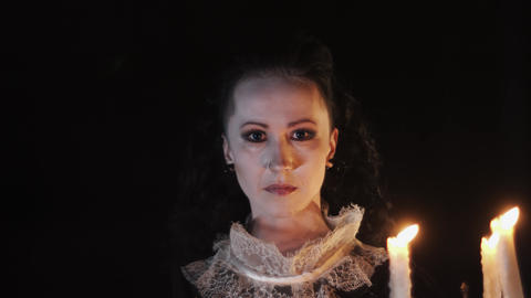 Portrait of woman in victorian dress staring in dark room with candelabrum Footage