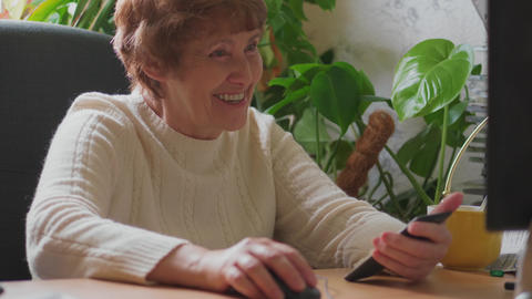 Senior woman working on computer, calling mobile, laughing Footage