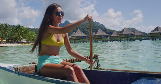 Adventure travel woman paddling in traditional Polynesian Outrigger Canoe Footage