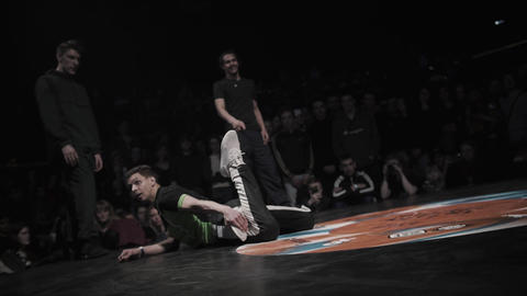 Short-haired bboy in green t-shirt and white sneakers performs breakdancing Live Action