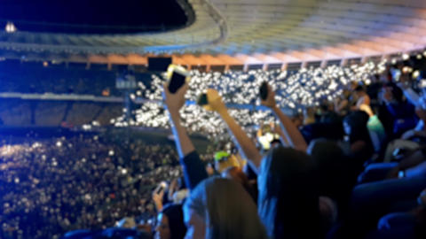 4k out of focus video of people on stadium tribunes waving with smartphones and Footage