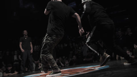 Young active men wearing sporty outfits perform cool breakdancing on stage Footage