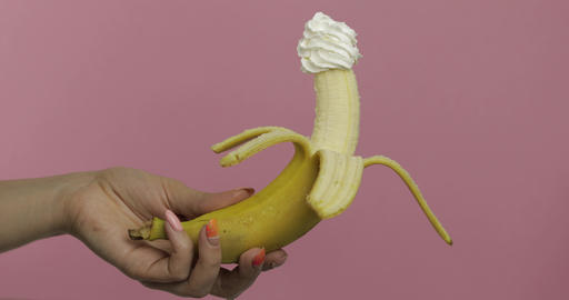 Woman hand holds banana with whipped cream on top of the fruit Footage