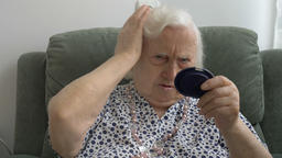 [alt video] Senior woman corrects her hair and looks in the mirror