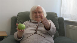 Happy old woman is showing green apple and thumb up. Healthy lifestyle Footage