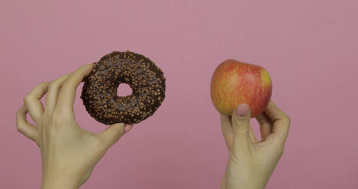 Hands holds donut and apple. Choice donut against apple. Healthy or junk food Footage