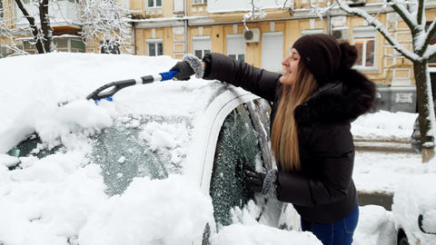 4k footage of beautiful smiling young woman removing snow from her automobile Footage