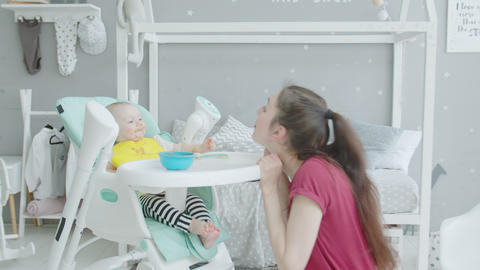 Playful mother making baby laugh during feeding Stock Video Footage