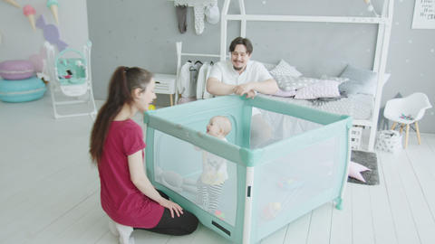 Happy parents rejoicing to baby getting up at home Footage