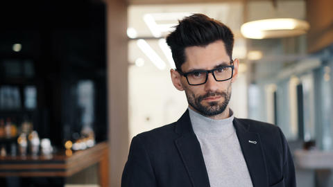 Portrait of businessman looking at camera with serious face standing in cafe Live Action
