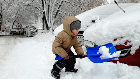 4k footage of little toddler boy sawing car stuck in snowdrift after snow storm Footage