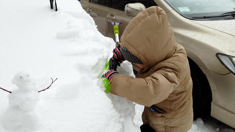 4k footage of little boy helping his father cleaning car from snow with brush Footage
