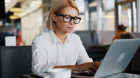 Corporate manager mature lady working with laptop in cafe... Stock Video Footage
