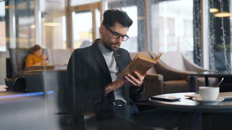 Smart man businessperson reading book in cafe focused on literature Footage
